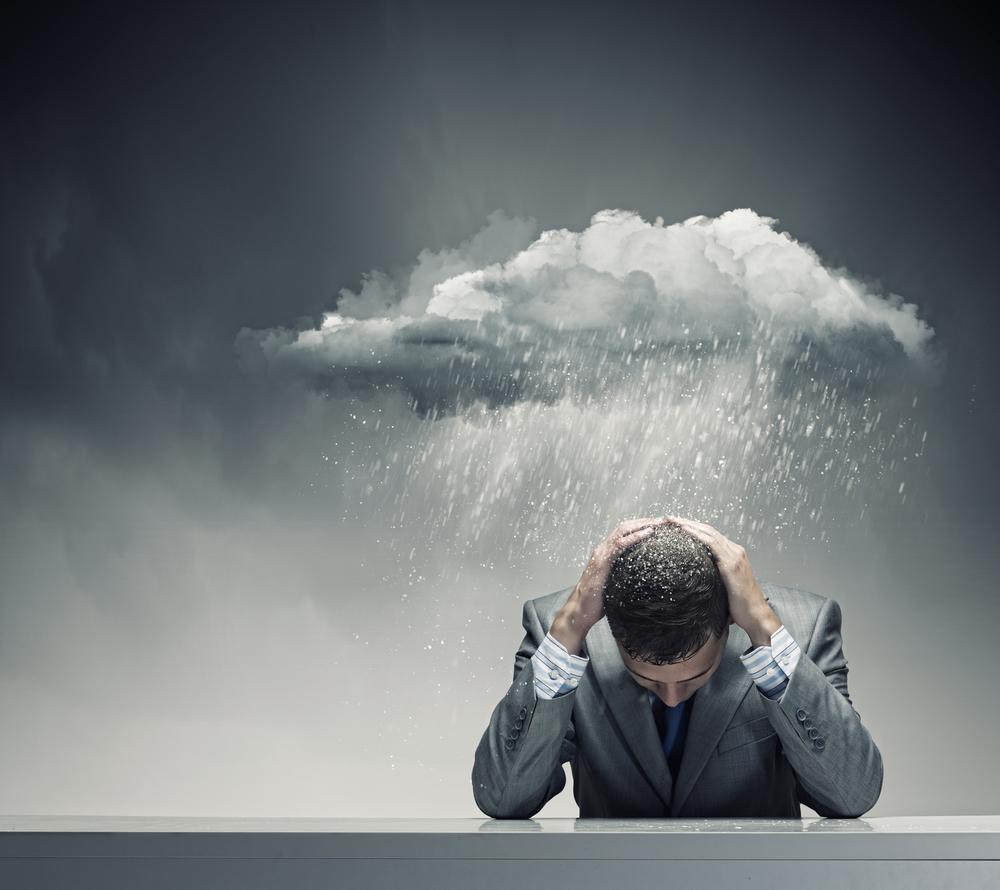 Depressed young businessman sitting wet under rain