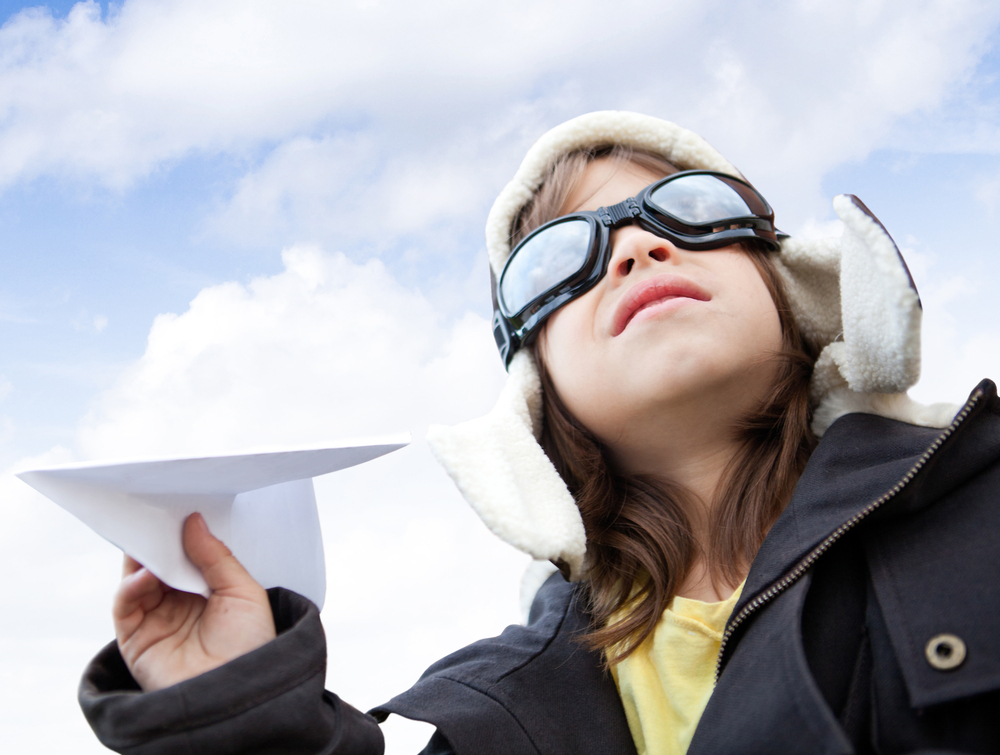 Young boy pilot holding a paper airplane looking at the sky-1
